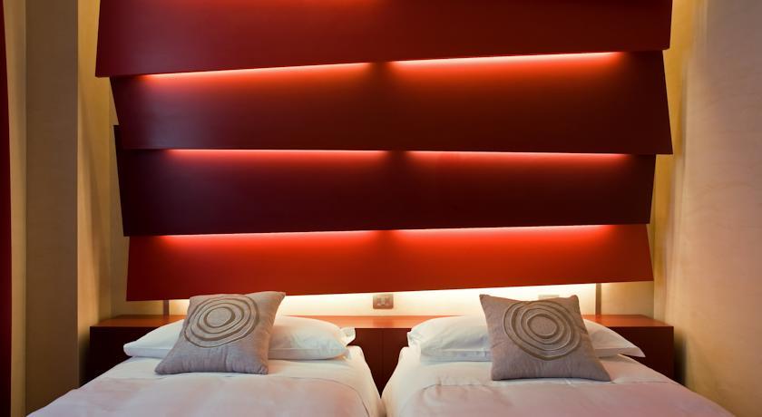 EOS Hotel - immagine letto con testata di design rosso fuoco a pannelli illuminati