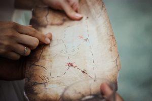 due mani che cercano insieme un punto su una mappa