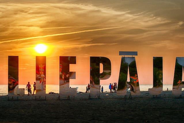 Liepāja, installazione riflettente sulla spiaggia_nome della città scritto con lettere a specchio che riflettono il panorama, il quale forma il nome della città grazie a questo materiale
