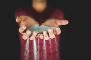 mani che lasciano cadere della sabbia. sfondo nero