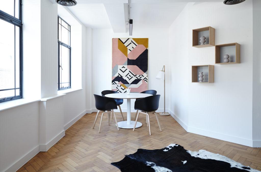 come rendere un locale accessibile - tavolo co 4 sedie in una stanza con parquet e design moderno, alla fine di un corridoio che si apre non con un angolo ma con una terza parete che lo taglia