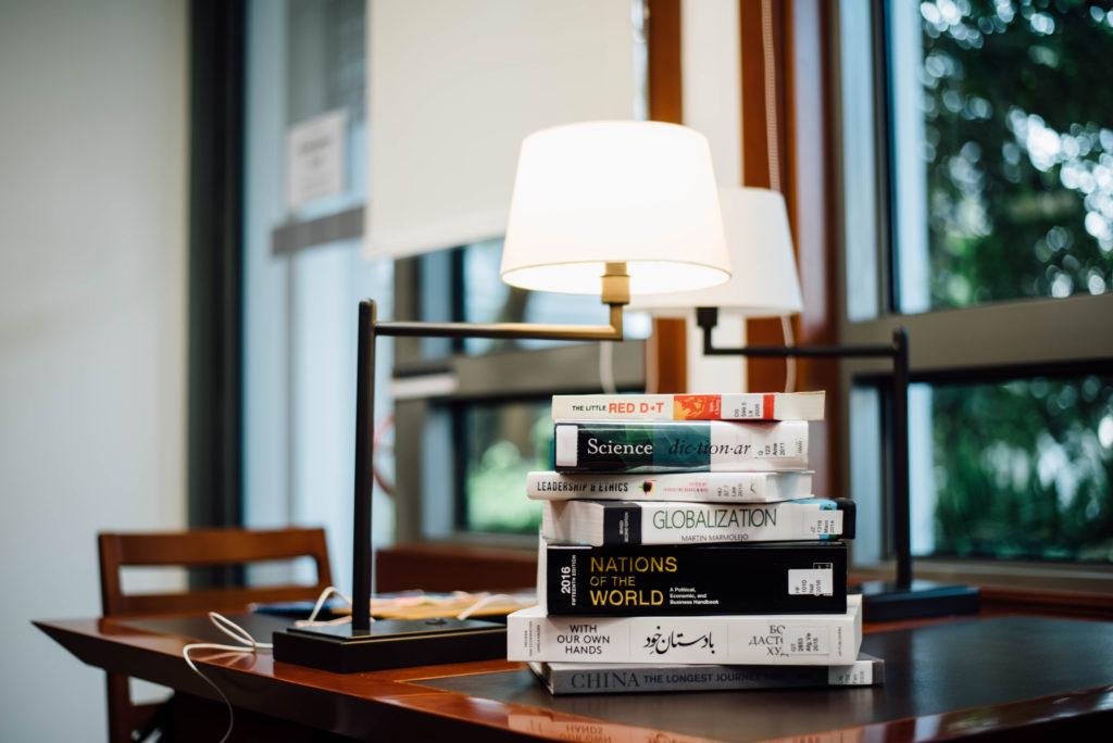 Libri su un tavolo sul quale è anche poggiata una lampada dal design classico