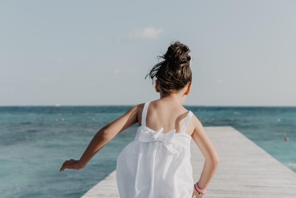 Bambina che corre verso il mare su una rampa di legno