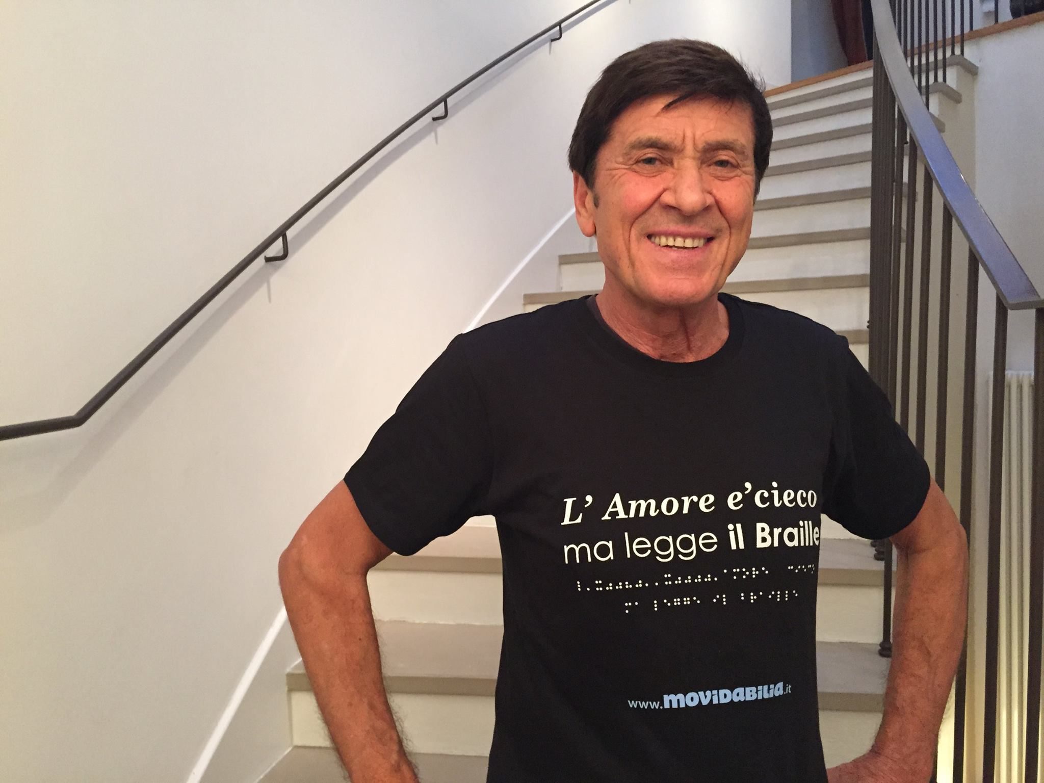 Gianni Morandi davanti alla scala di casa sua, con la maglietta di Accessibility is cool