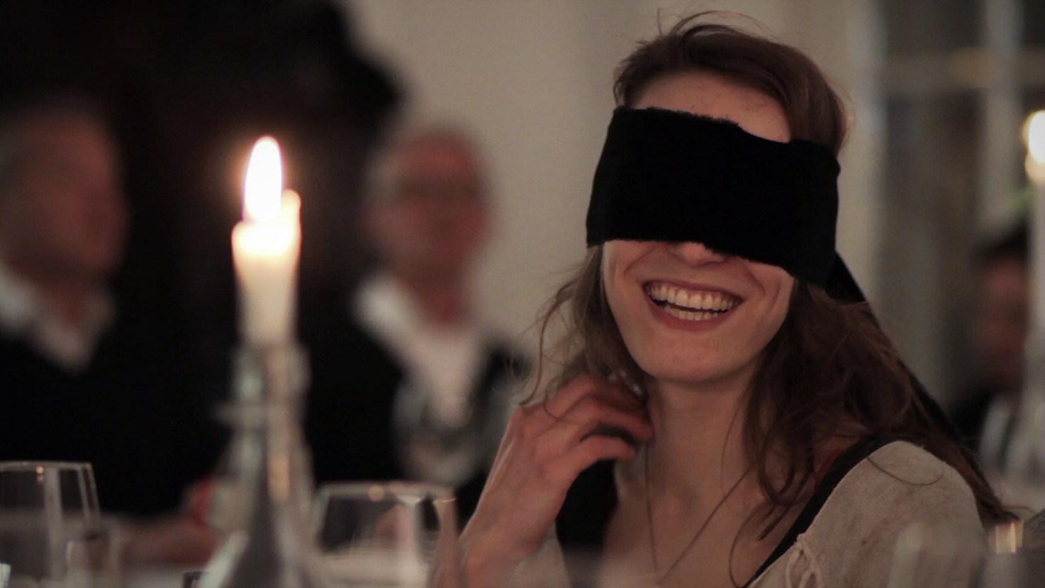 cena al buio - donna bendata ad una cena a lume di candela