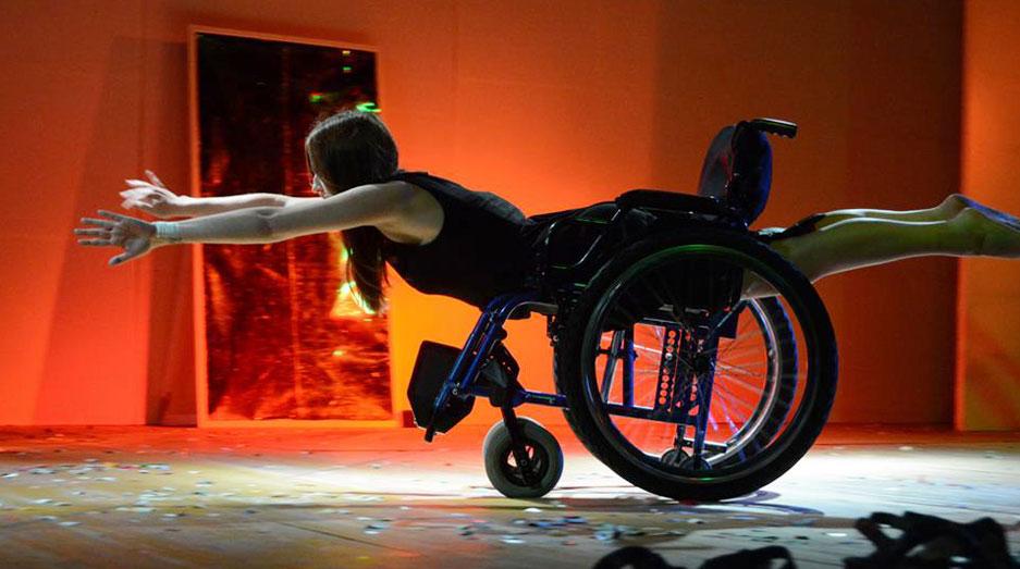 Ragazza che finge di volare su una sedia a rotelle - performance teatrale