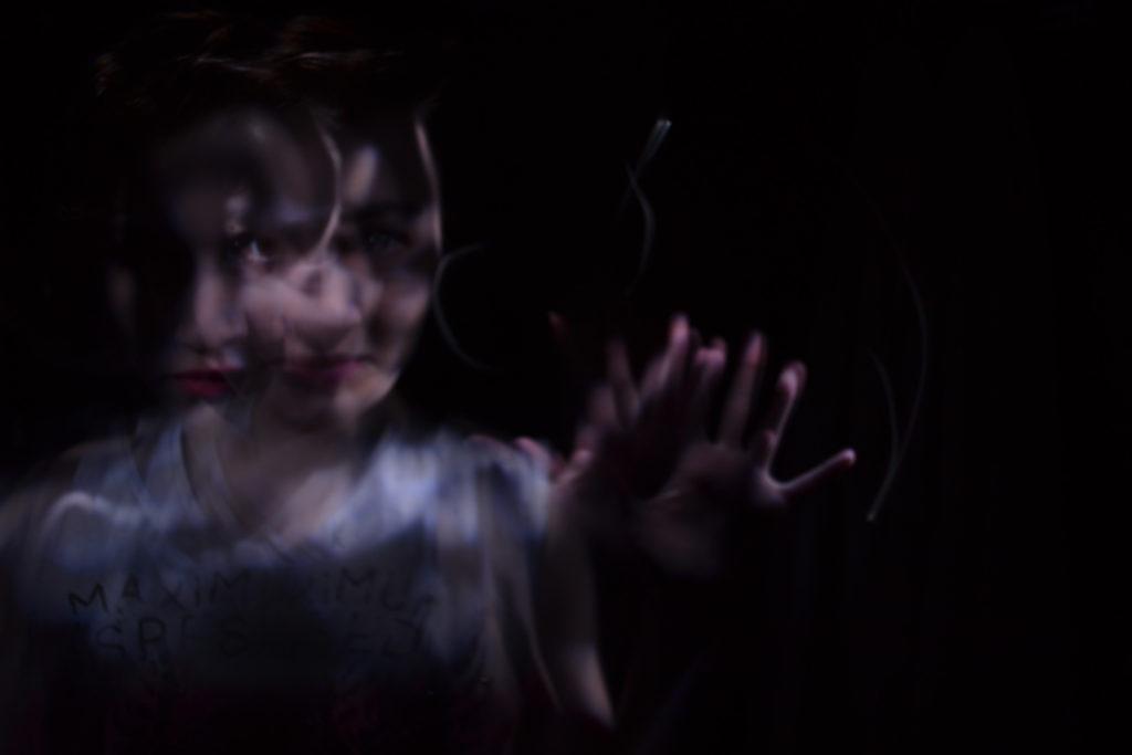 Donna nel buio, si muove serena mentre l'aria vibrante la fa apparire un po' mossa. La mano protratta in avanti la aiuta a percepire l'aria e le vibrazioni