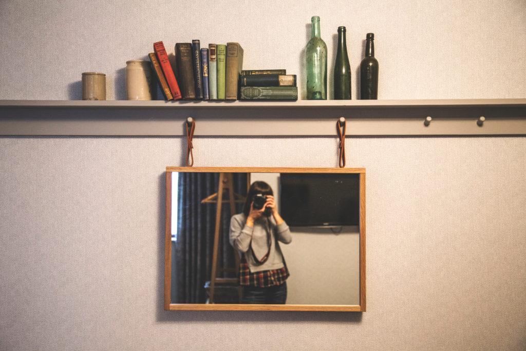 ragazza che si fotografa in uno specchio; ha una macchina professionale, lo specchio è quadrato con bordi in legno e pende da una mensola minimal con bottiglie vuote e libri.
