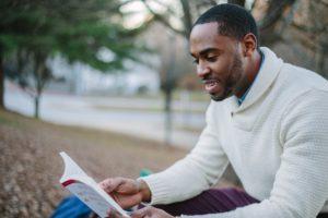 ragazzo di etnia africana seduto all'aperto mentre legge