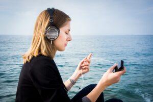 ragazza con cuffie e e cellulare al mare_audio descrizione eventi culturali