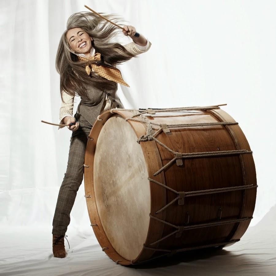 Eveline Glennie, capelli lunghi e grigi, sorridente ed elegante in abito grigio suona un enorme tamburo