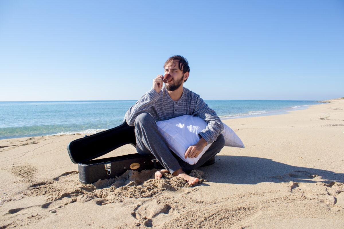 domenico desantis che beve un caffe seduto in spiaggia con chitarra e cuscino
